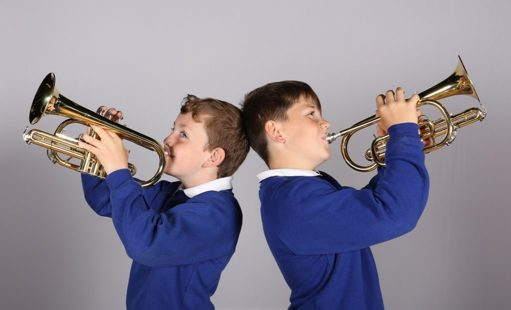 Two boys back to back playing trumpets